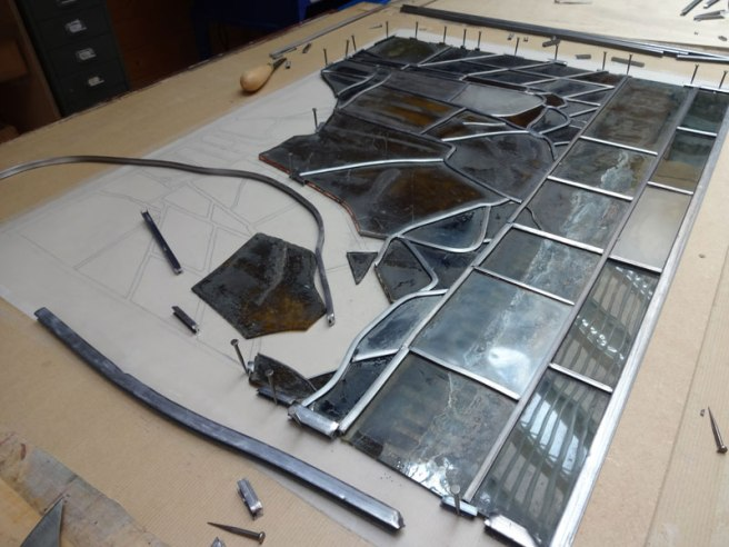 A panel during assembly – note the design attached to the board below the glass, and the nails holding the pieces in place.
